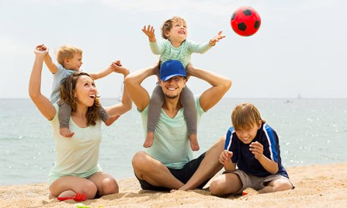 Positive family of five playing at sea beach and resting together